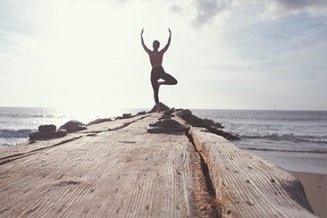 rear view of a woman in a yoga pose on a dock over the water